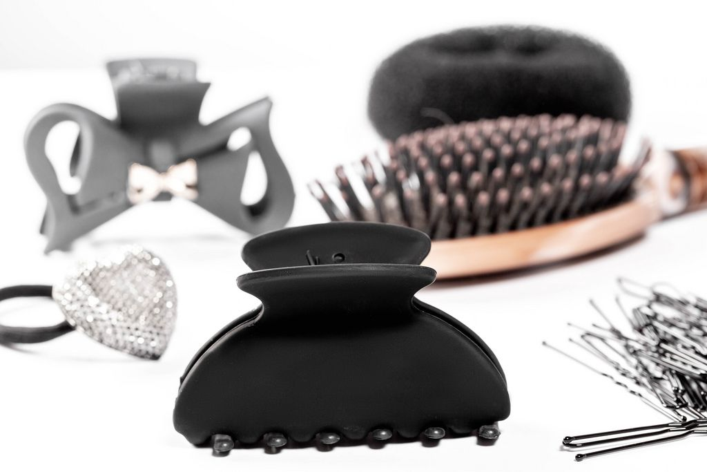 Black hair clips and hair bands with hairbrush on white background