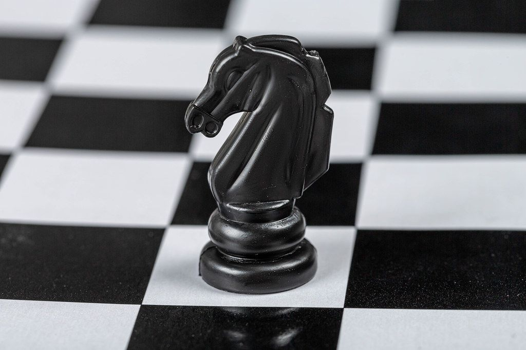 Black horse chess piece on the board background (Flip 2019)