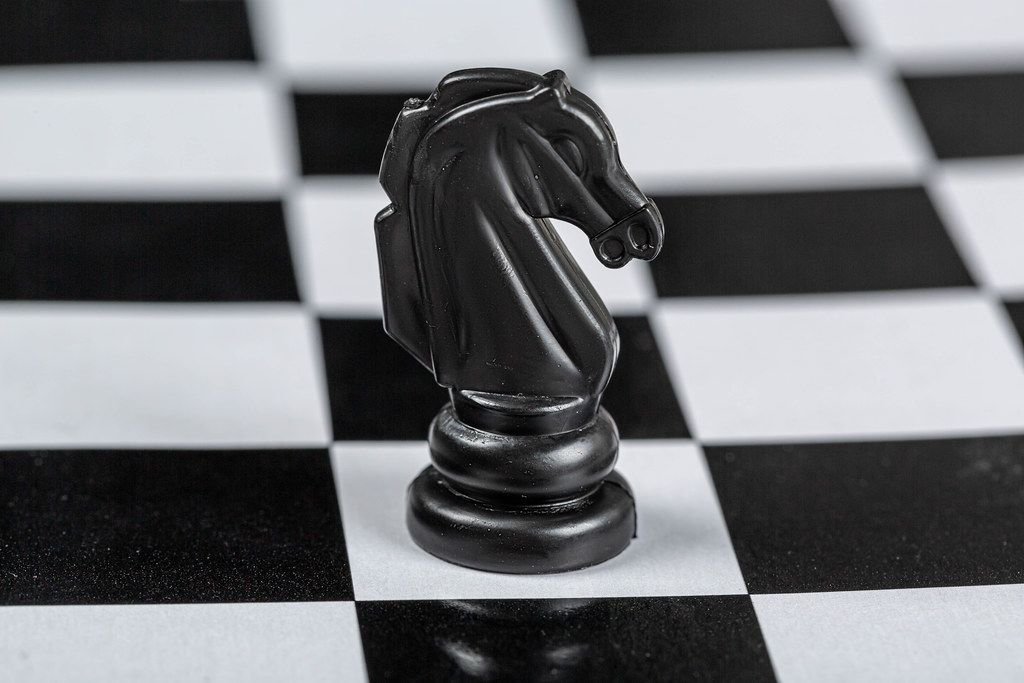 Black horse chess piece on the board background