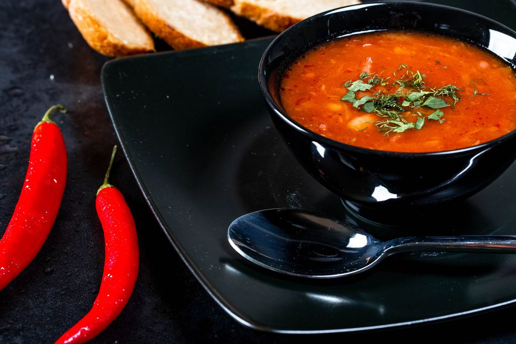 Black tureen with beet-tomato soup and spoon