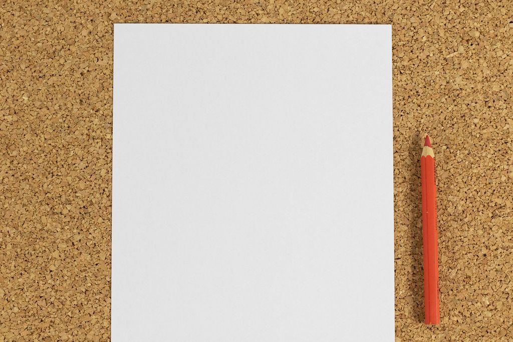 Black white paper with red pencil on cork background