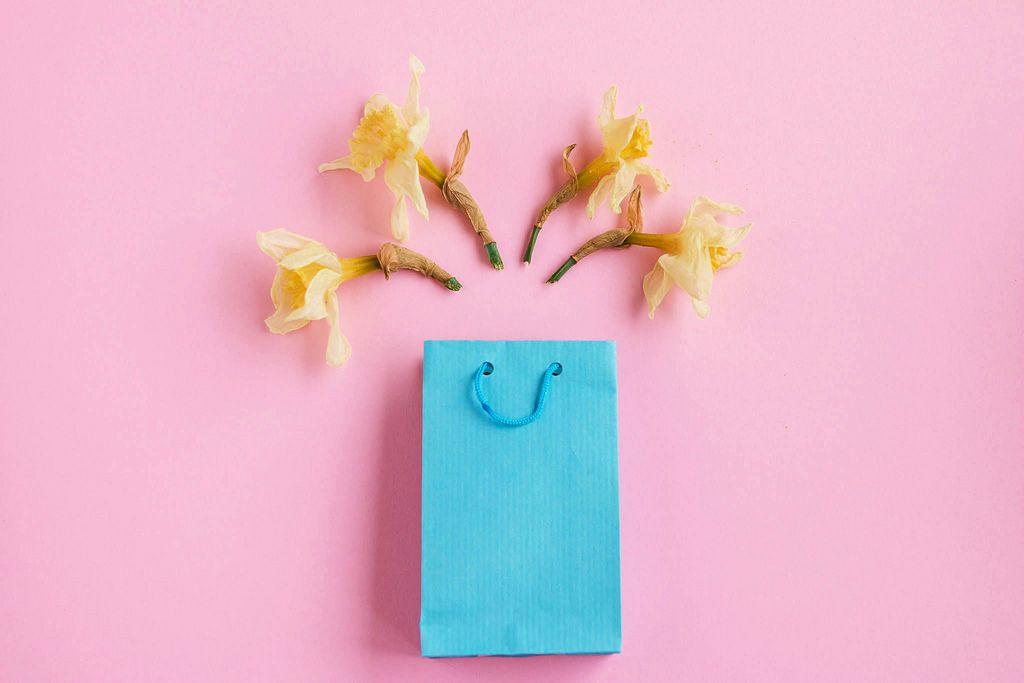 Blaue Geschenktüte und gelbe Frühlingsblumen vor rosafarbenem Hintergrund