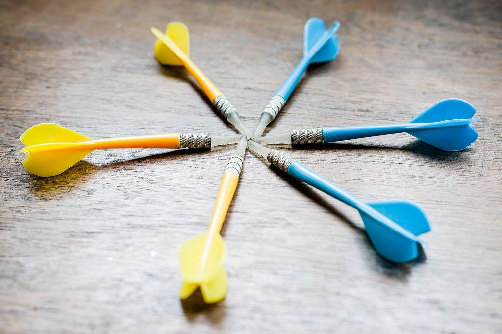 Blaue und gelbe Darts zeigen Richtung Mitte