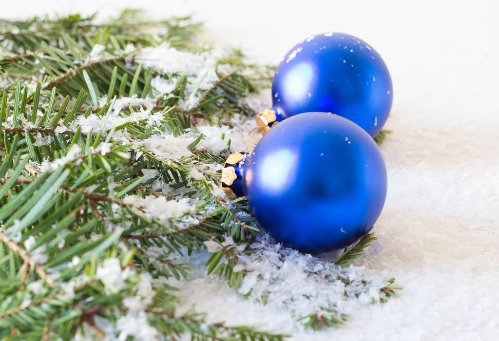 Blaue Weihnachtsbaumkugeln und ein Ast bedeckt mit Kunstschnee
