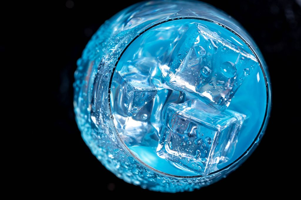 Blauer Cocktail mit quadratischen Eiswürfeln in einem Glas, aus der Vogelpserspektive fotografiert