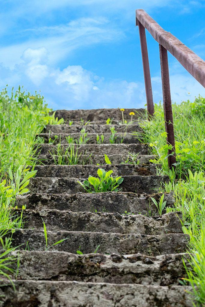 Blauer Himmel mit Wolken über einer Steintreppe inmitten von Gras, auf einem Hügel