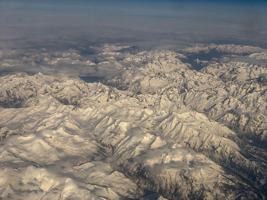 Blick auf die Alpen durch das Flugzeugfenster