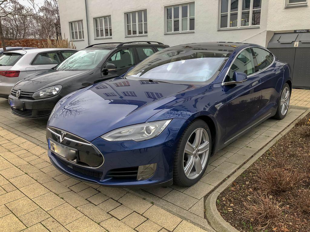 Blick auf Front und Seite eines Autos der Marke Tesla Model S 85D vor Haus geparkt