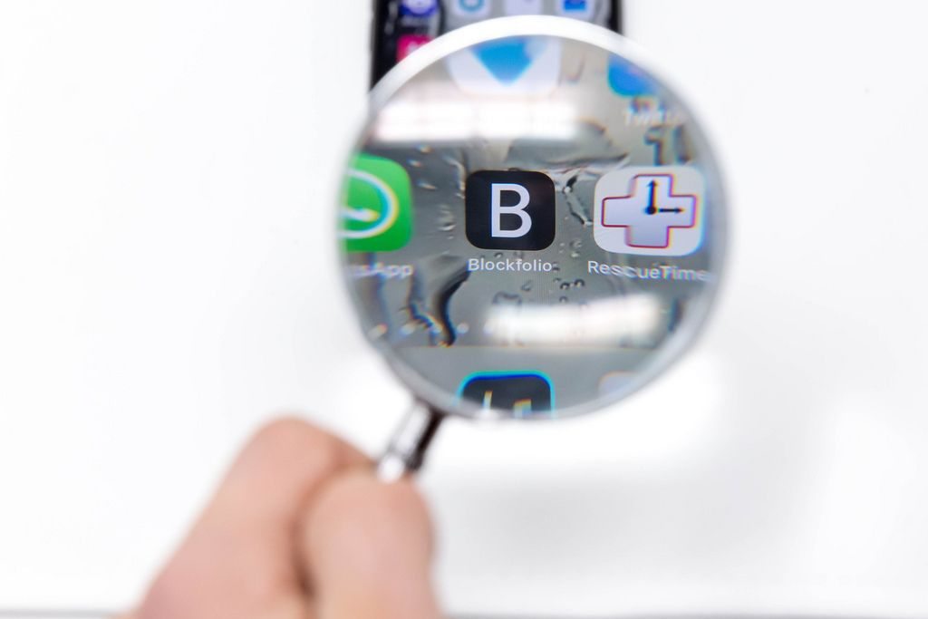 Blick durch Lupe auf Blockfolio App Logo auf Mobiltelefon vor weißem Hintergrund