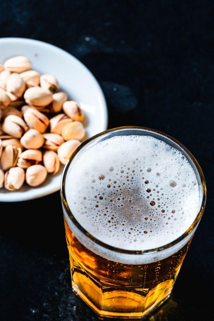 Blick von oben auf Bier und Schale mit ungeschälten Pistaziennüssen