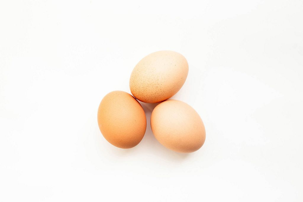 Blick von oben auf drei braune Eier vor weißem Hintergrund