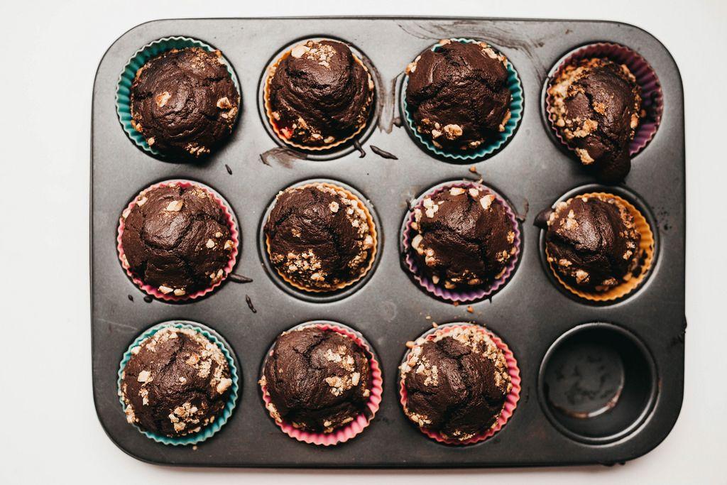 Blick von oben auf frisch gebackene Schokoladen-Muffins mit Nüssen in farbigen Kuchenförmchen aus Papier in schwarzer Muffin-Backform