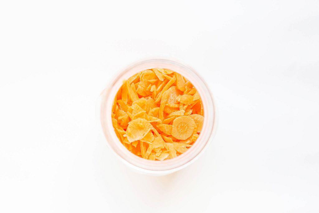 Blick von oben auf geschnittene Karotten in Glas vor weißem Hintergrund