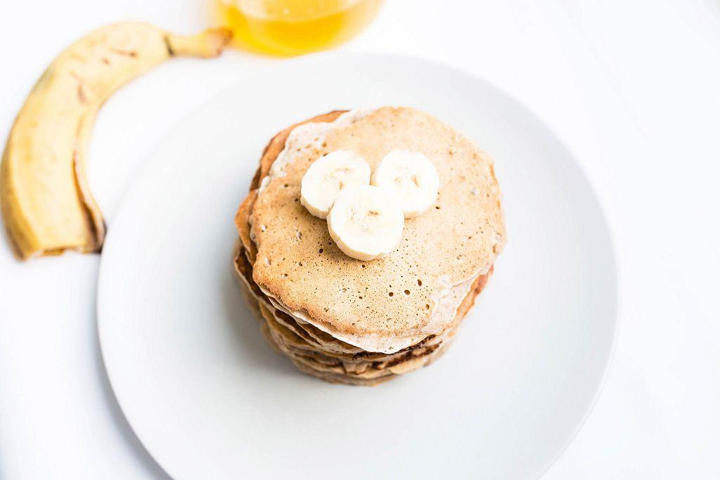 Blick von oben auf gestapelte, vegane Pfannkuchen mit Bananenstücken auf weißem Teller