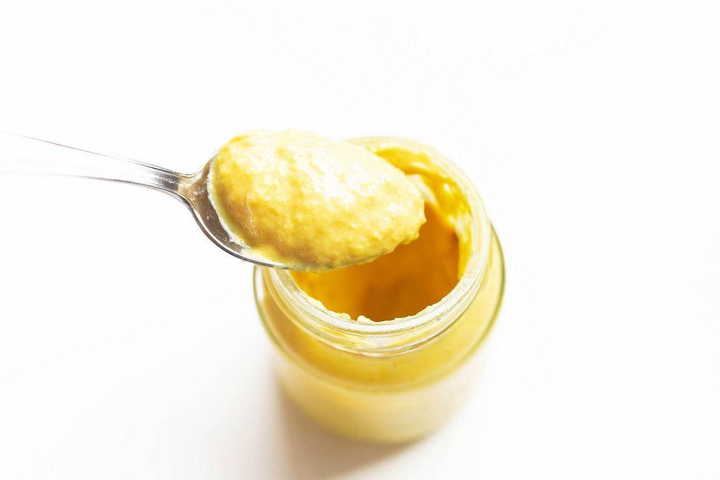 Blick von oben auf Löffel der Senf aus Senfglas nimmt vor weißem Hintergrund