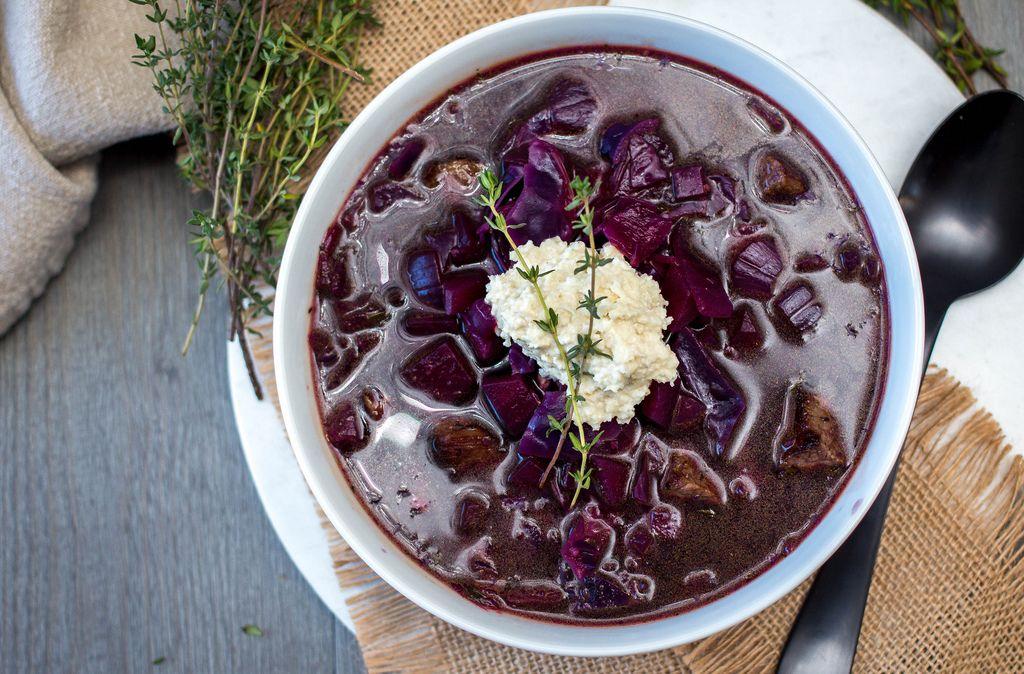 Blick von oben auf rote Borschtsch Suppe aus Rotkohl und Suppenfleisch mit Rosmarin