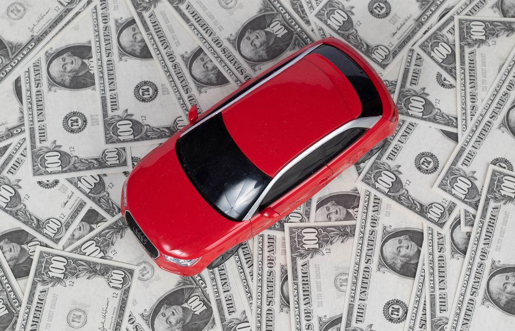Blick von oben auf rotes Auto auf Hintergrund aus Banknoten