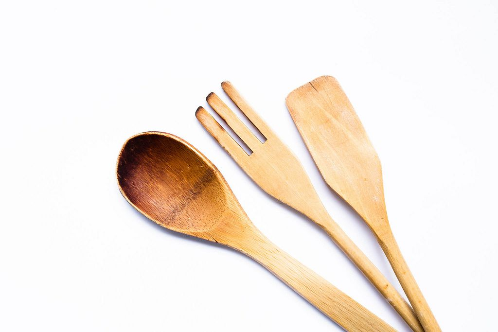 Blick von oben auf Sortiment an Kochbesteck aus Holz wie Kochlöffel und Spatel vor weißem Hintergrund