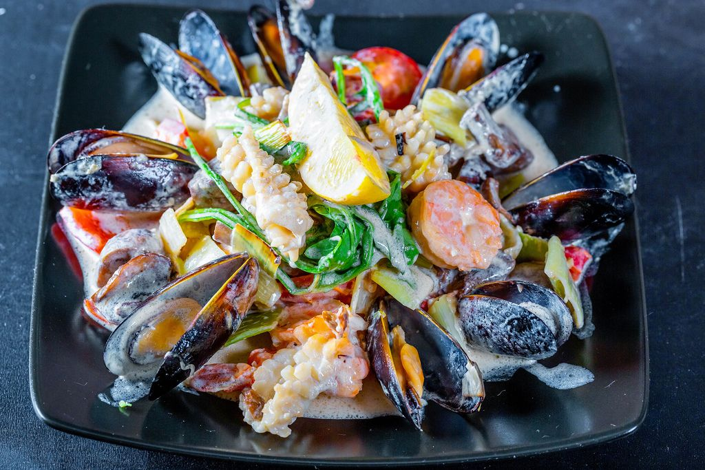Blick von oben auf Teller mit frischen Meeresfrüchten und Gemüse in Cremesoße