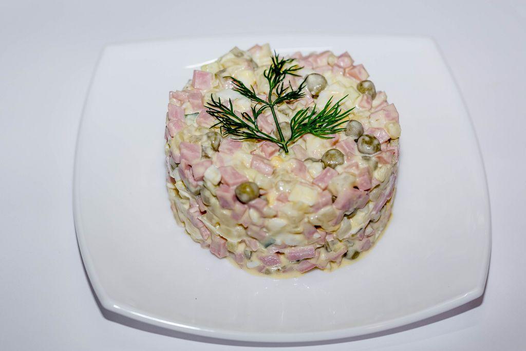 Blick von oben auf Teller mit russischem Salat vor weißem Hintergrund