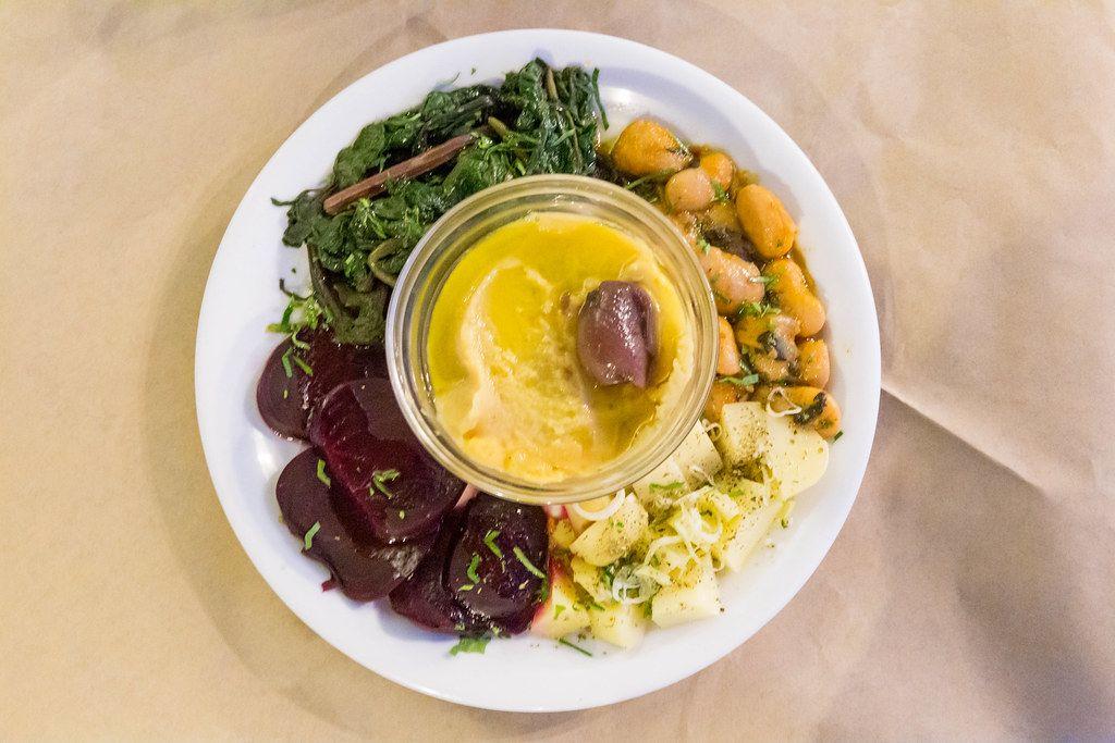 Blick von oben auf vegetarisches Favapüree mit roter Bete, weißen Bohnen, Spinat und Kartoffeln