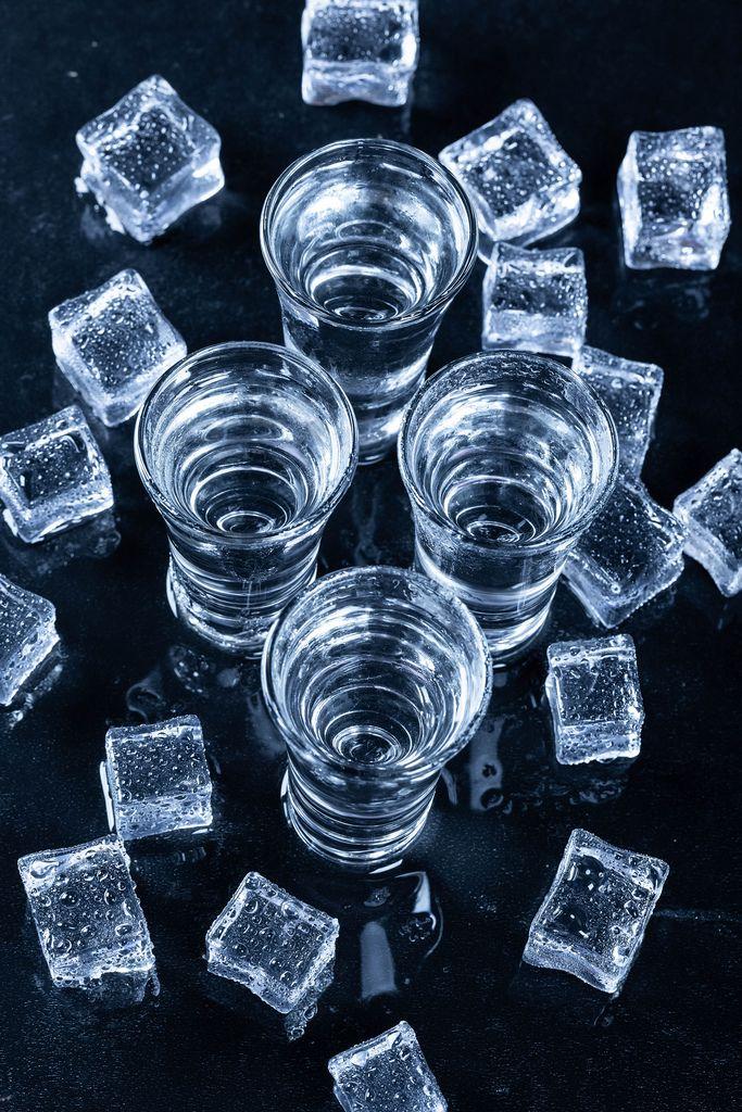 Blick von oben auf vier Gläser mit kaltem Wodka umringt von Eiswürfeln auf schwarzem Hintergrund