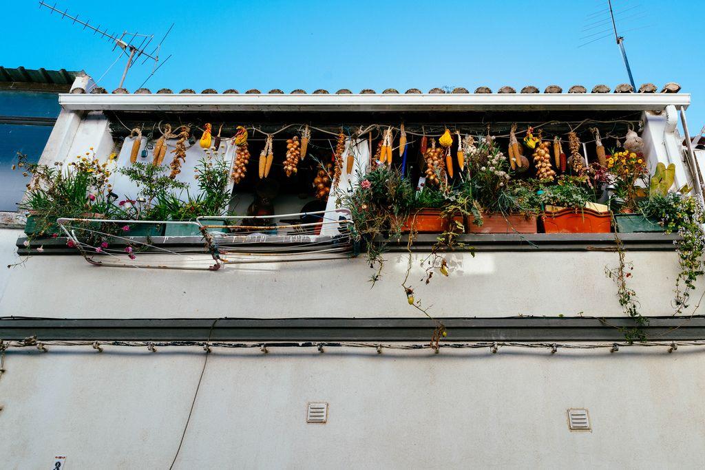Blick von unten auf Balkon mit zum Trocknen aufgehängten Zwiebeln und Maiskolben in Lagos, Portugal