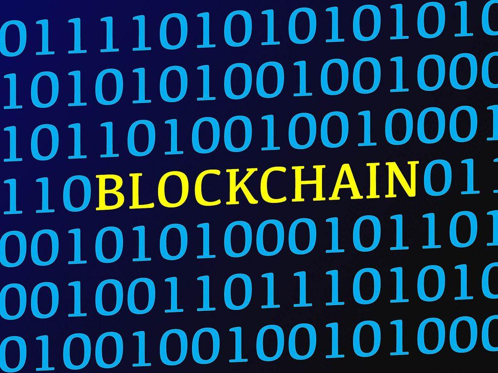 Blockchain text between blue binary data on screen