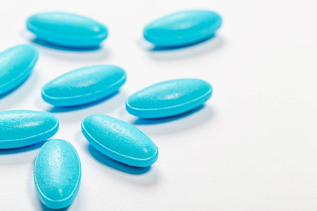 Blue antibiotic pills on white background