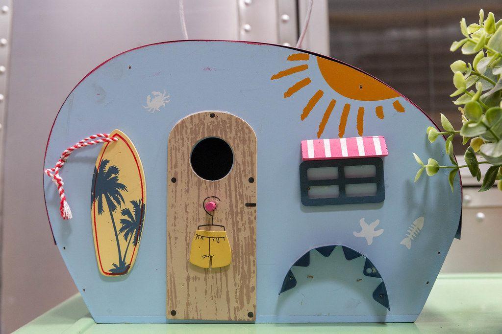 Blue miniature caravan with beach flair, a surfboard and summer painting