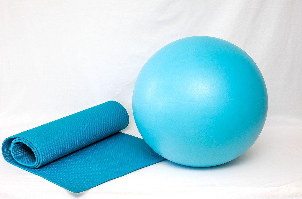 Blue Yoga Mat next to Blue Yoga Ball on White Background
