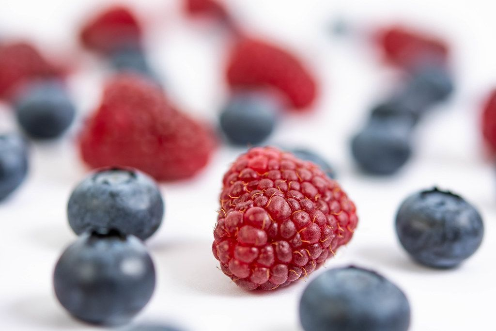 Blueberries and Raspberries on the white background table