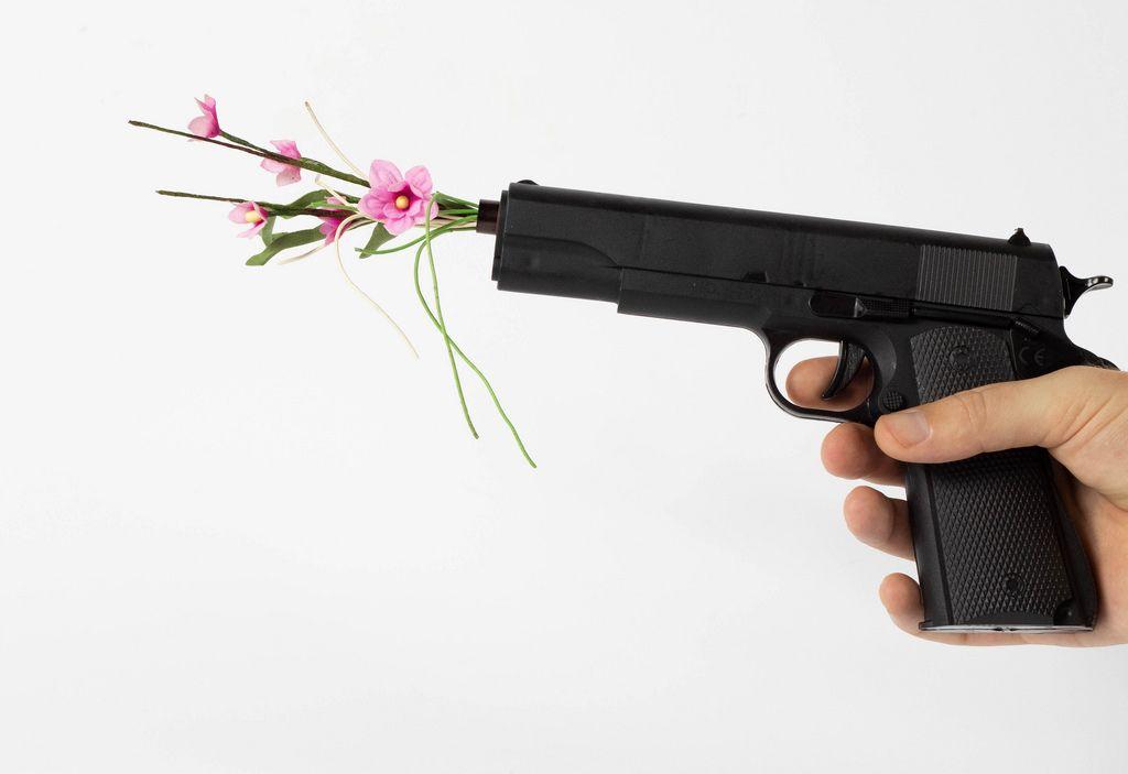 Blumen ragen aus dem Lauf einer Pistole heraus