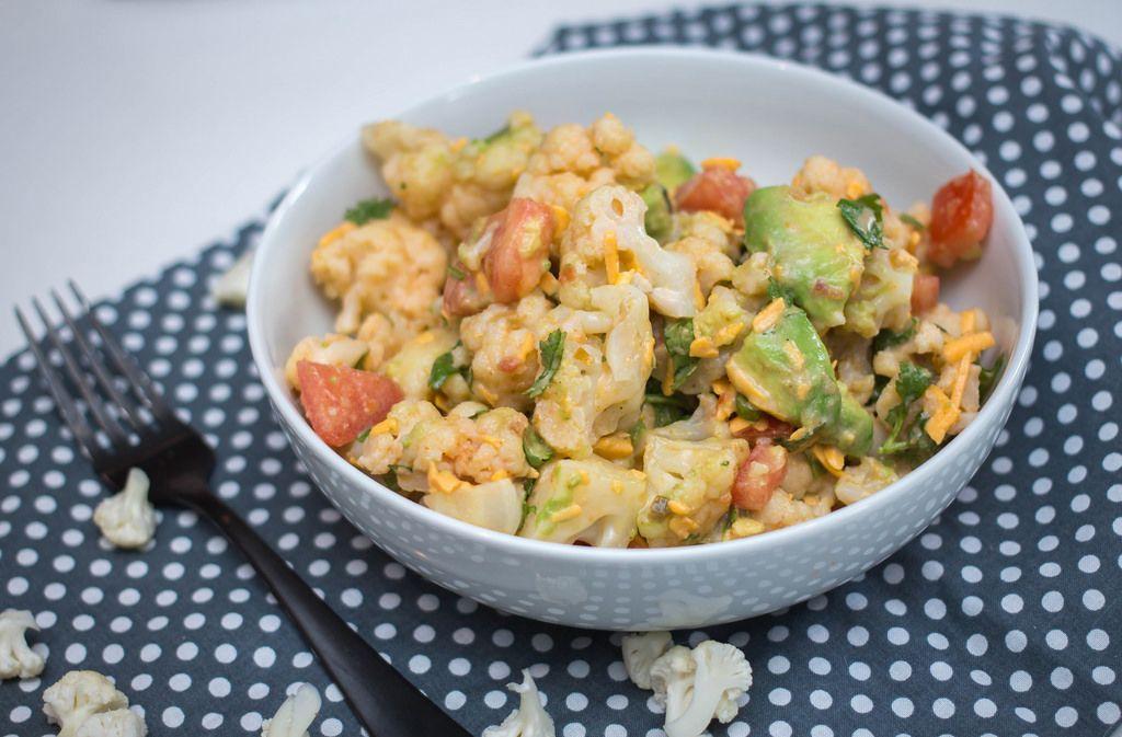 Blumenkohl Salat, mit Avocado, Möhren und Tomaten in einer Schale auf gepunktetem Platzdeckchen und schwarzer Gabel