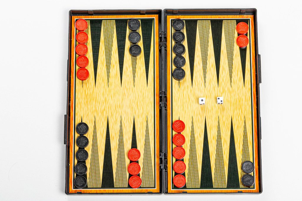 Board for playing backgammon with pieces and dice on a white background. Top view