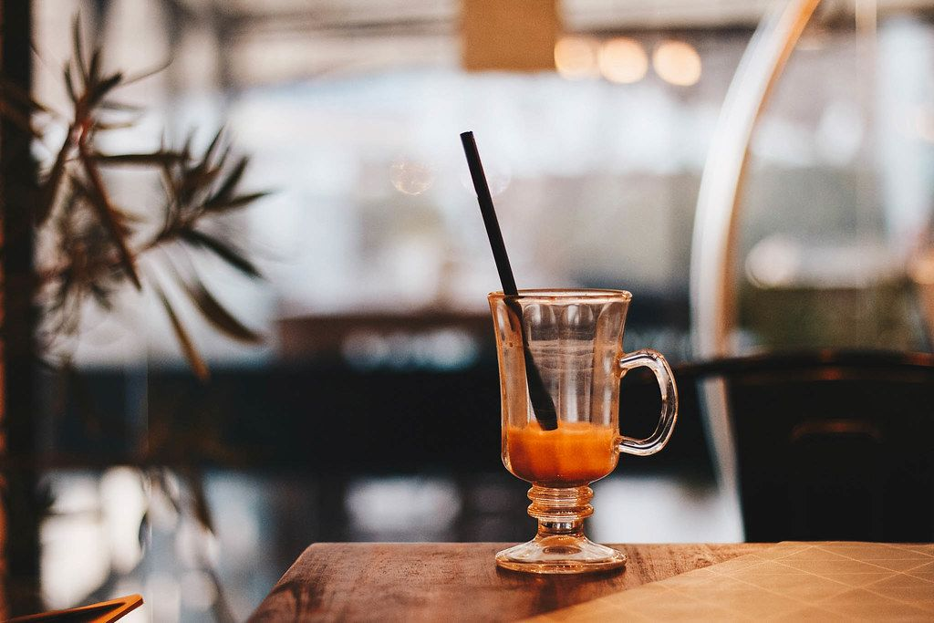 Bokeh Photo of Glass Cup of Coffee on Wooden Table with Cafe in the Background