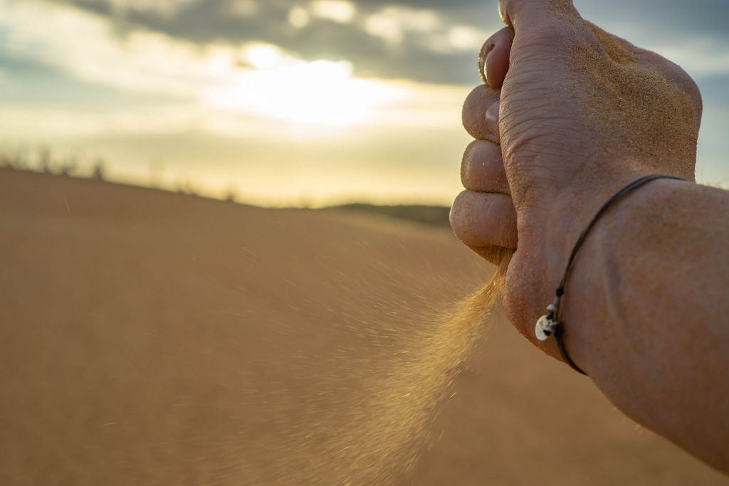 Bokeh Shot of a Hand dropping Sand in the Desert with Sunset in the Background (Flip 2019) (Flip 2019) Flip 2019