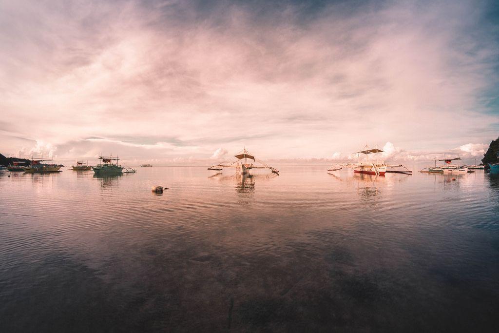 Boote liegen am Strand in Sipalay bei Sonnenuntergang an
