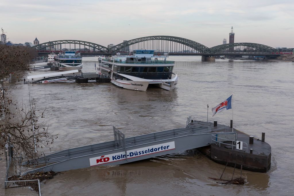 Bootssteg und Schiffe bei Hochwasser mit der Hohenzollernbrücke im Hintergrund
