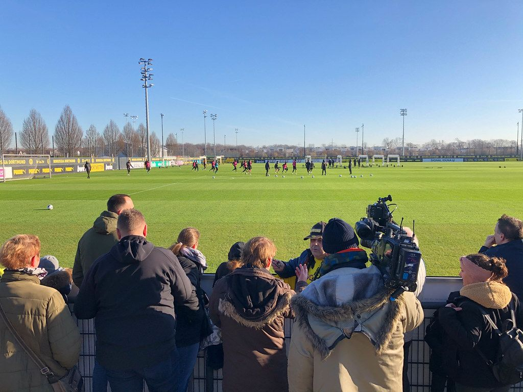 Borussia Dortmund fans and a camera operator attend the public training of the Bundesliga team