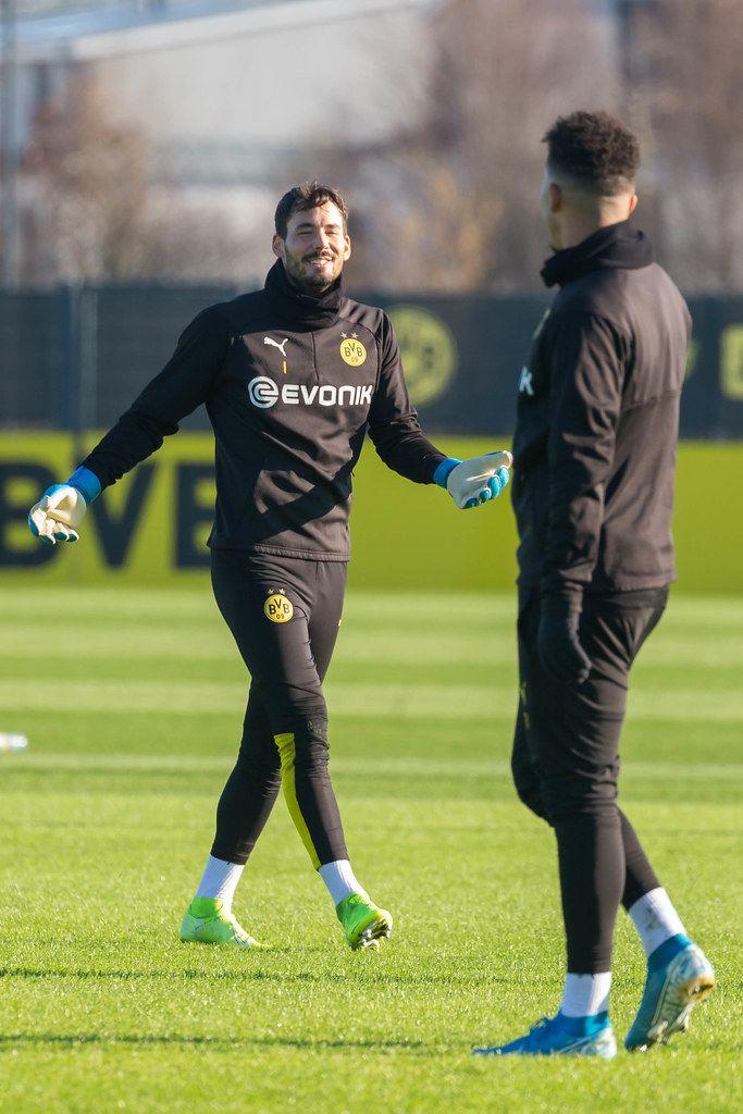 Borussia Dortmund goalkeeper Roman Bürki makes a gesture with open arms and addresses Jadon Sancho