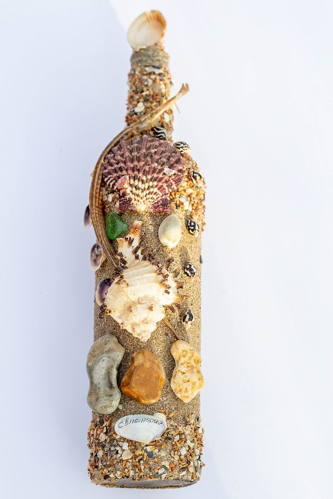Bottle decorated with a variety of sea shells