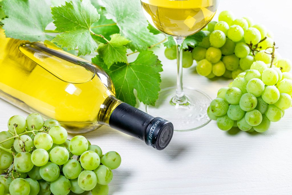 Bottle of white wine, glass, green grapes and leaves on white table (Flip 2019)