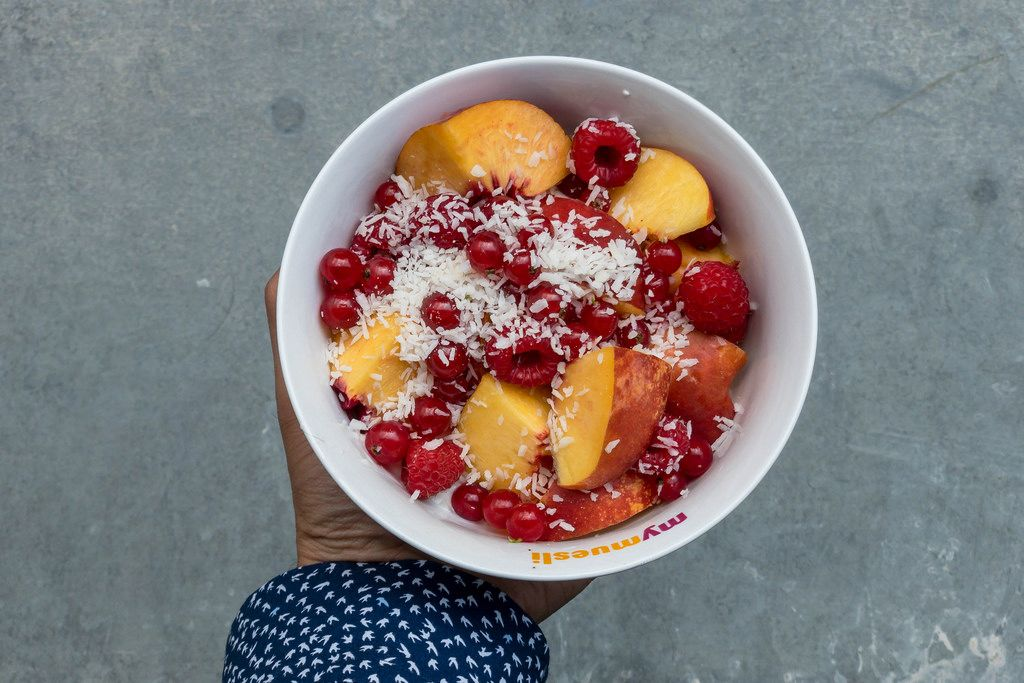 Bowl with raspberries, currants, peach and shredded coconut