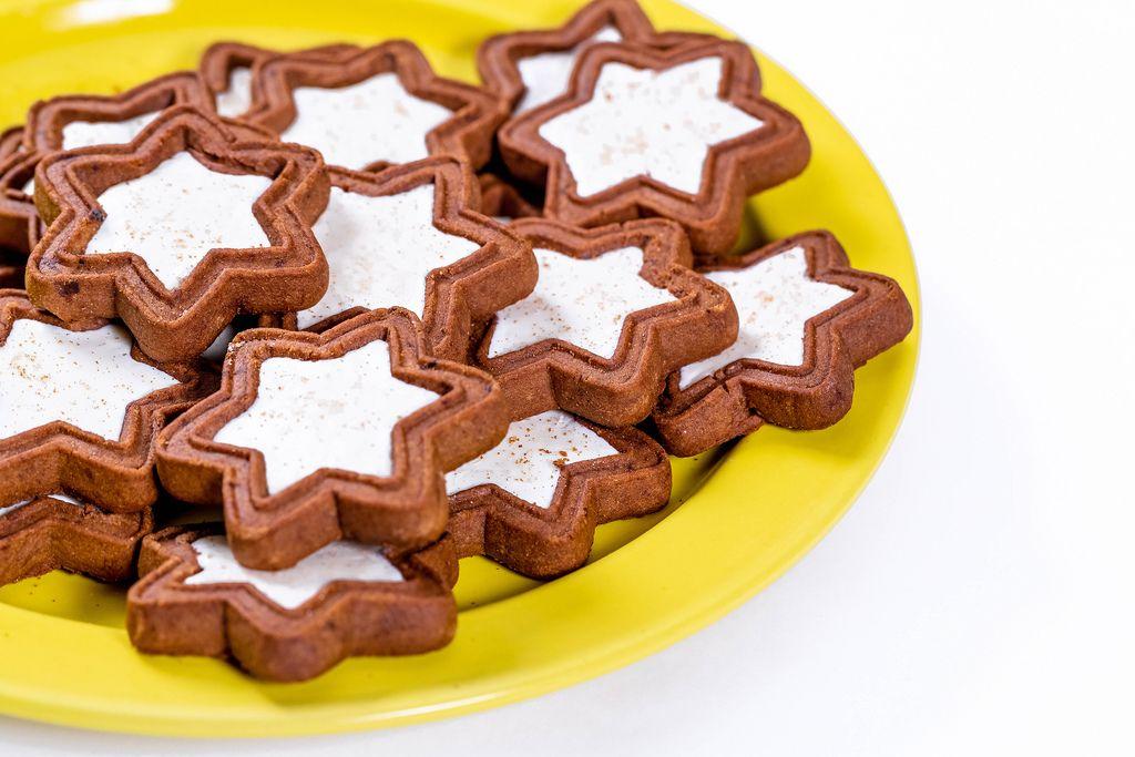 Braun-weiße, zu Sternen geformte Weihnachtsplätzchen auf gelbem Teller und weißem Hintergrund