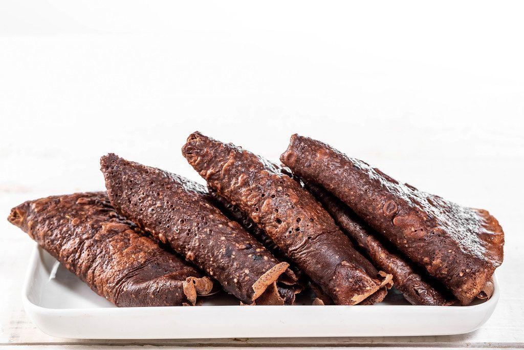 Braune Schokoladen-Pfannkuchen auf einem weißen Teller