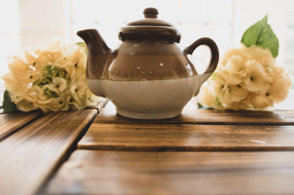 Braune Teekanne aus Keramik mit weißen Blumensträußen auf einem Holztisch