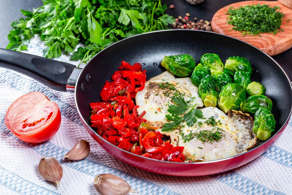 Breakfast in the pan-fried eggs with vegetables and herbs on the table
