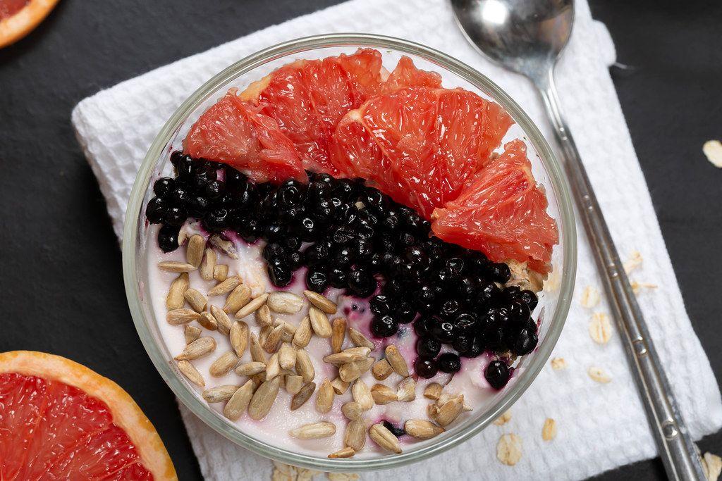 Breakfast oatmeal with yogurt, grapefruit, black elderberry and sunflower seeds