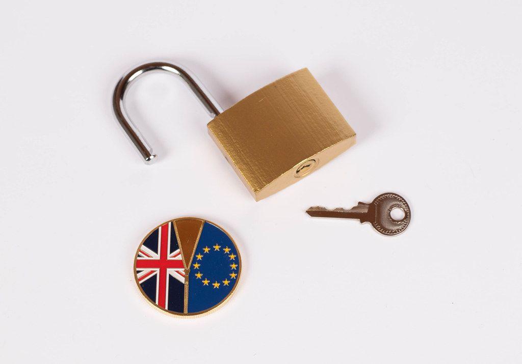 Brexit Medaille mit offenem Vorhängeschloss und Schlüssel vor weißem Hintergrund